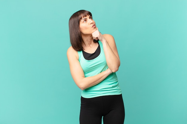 Atleetvrouw die denkt, zich twijfelachtig en verward voelt, met verschillende opties, zich afvragend welke beslissing ze moet nemen