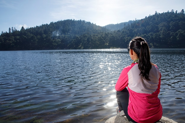 Atleta descansando a la orilla de un lago sentada sobre un piedra despus de correr in el bosque