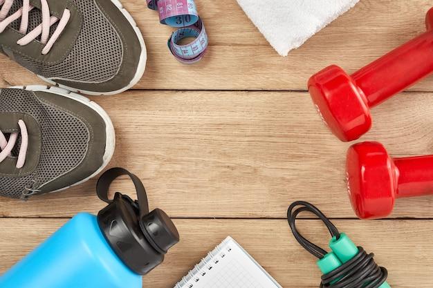 Atleten apparatuur halter sport waterflessen kladblok springtouw sneakers op houten achtergrond