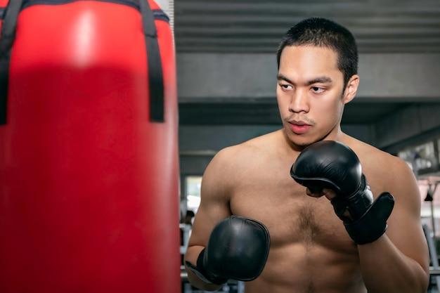 Atleten aziatische man bokser training op een bokszak op fitness gym