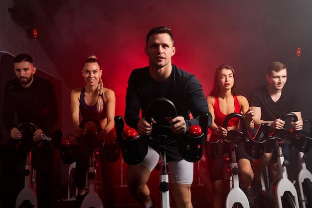 Atleten mensen trainen fietsen in de sportschool, met de bedoeling van gezondheidszorg. blanke mannen en vrouwen schreeuwen om het lichaam gezond te maken met strakke spieren en het gewicht te verminderen. mannetje in het midden