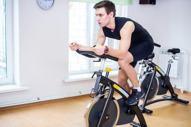 Atletenmens die in de gymnastiek fietsen