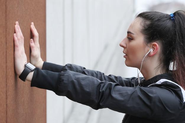 Atletenvrouw die het uitrekken in de straat doen zich