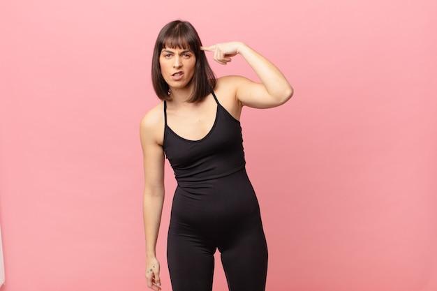 Atletenvrouw die zich verward en verbaasd voelt en laat zien dat je gek, gek of gek bent