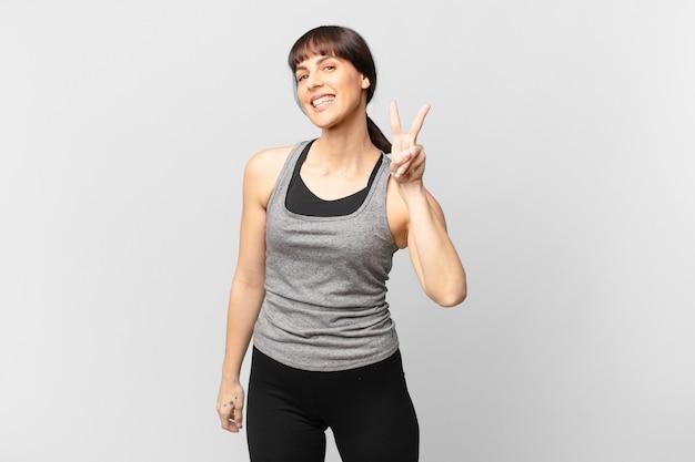 Atletenvrouw lacht en ziet er gelukkig, zorgeloos en positief uit, gebarend overwinning of vrede met één hand