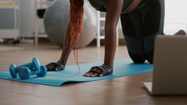 Atletenvrouw met zwarte huid die lopende plankoefening doet op yogakaart in woonkamer die laptop computer gebruikt