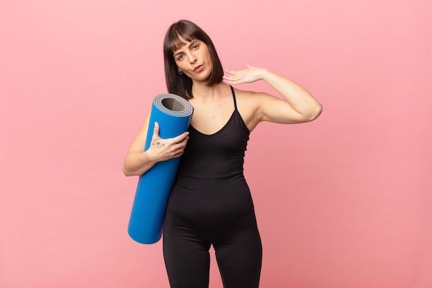 Atletenvrouw voelt zich gestrest, angstig, moe en gefrustreerd, trekt aan de nek van het shirt, ziet er gefrustreerd uit met een probleem
