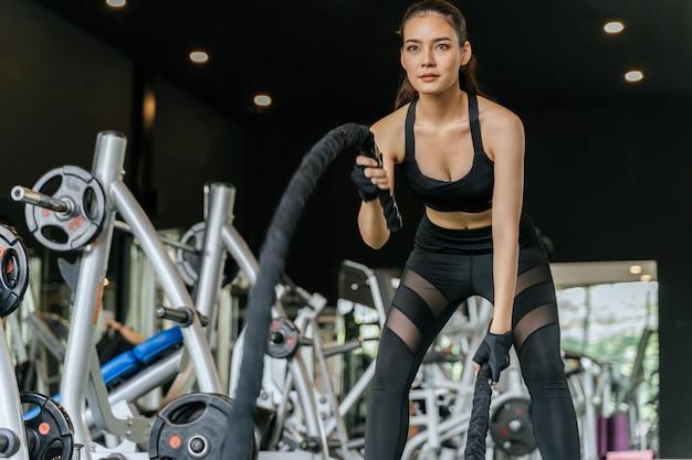 Atletisch aziatisch jong sterk vrouwen slank lichaam die en met slagtouw opleiden in geschiktheidsgymnastiek voor goede gezondheid uitwerken