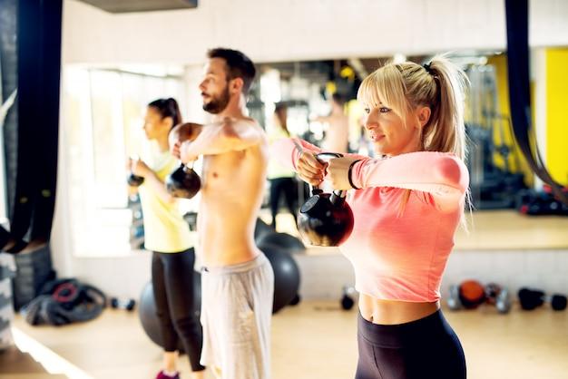 Atletisch fitte mensen doen schoudertraining met de kettlebell.