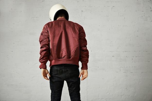 Atletisch jong model in skinny jeans, terracotta bomberjack en witte motorhelm geïsoleerd op wit, achter schot