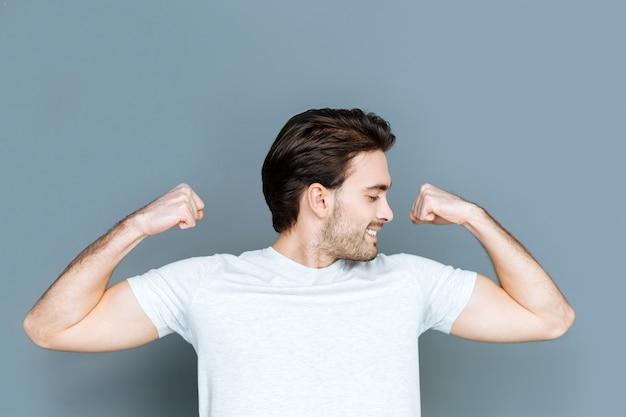 Atletisch lichaam. aantrekkelijke aardige sterke man die zijn handen omhoog houdt en glimlacht terwijl hij zijn biceps toont