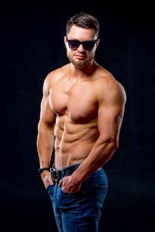Atletisch lichaam. half gedraaide modelman poseert voor de camera op de donkergrijze achtergrond. studiofoto. sterke gespierde man. detailopname.