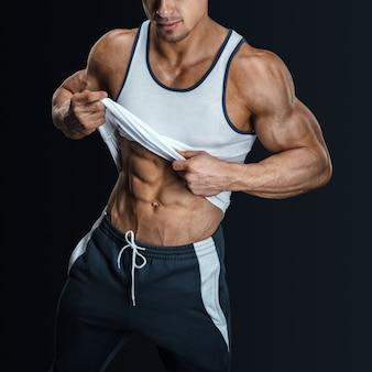 Atletisch mannelijk lichaam in sportkleding. man trekt tanktop omhoog om gespierde buikspieren te onthullen.