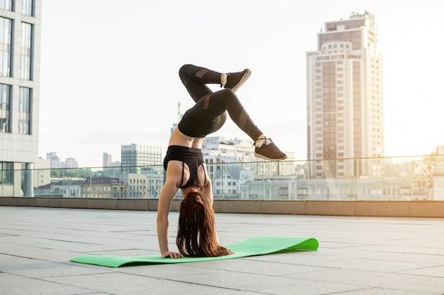 Atletisch meisje bezig met atletiek in de stad, ze traint 's ochtends op straat, een vrouw doet een oefening bij zonsondergang