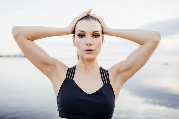 Atletisch meisje dat met mouwloos onderhemd een stuk op het strand doet