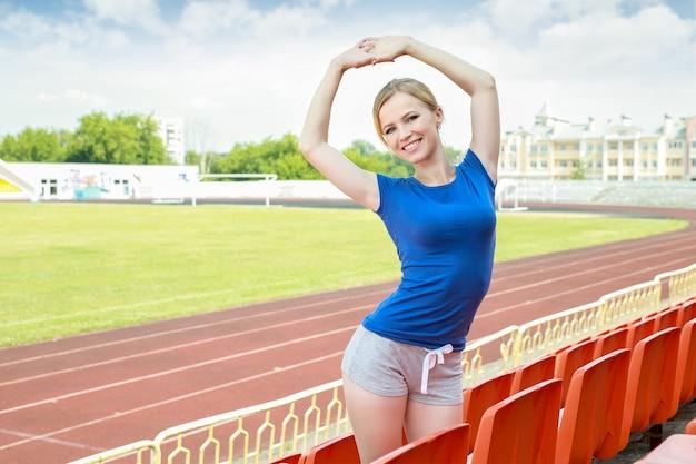Atletisch meisje dat oefening op voetbalveld neemt