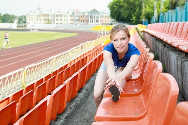 Atletisch meisje dat uitrekkende oefening buitenshuis neemt