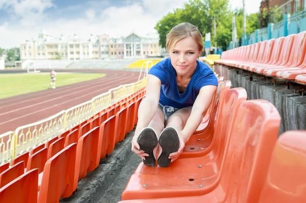 Atletisch meisje dat uitrekkende oefeningsstadion buitenshuis neemt