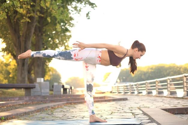Atletisch meisje doet geavanceerde yoga-asana op de fitnessmat buitenshuis.
