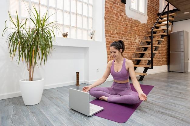 Atletisch meisje doet yoga meditatie houding voor haar laptop thuis. concept van online lessen.