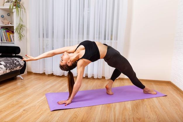Atletisch meisje doet yoga oefening in de opleiding van het meisje in de woonkamer