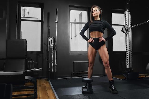 Atletisch meisje hurkt met een barbell. mooi fitnessmodel dat oefeningen op de benen doet. doet squats met een lading. mooie benen die het doel bereiken.