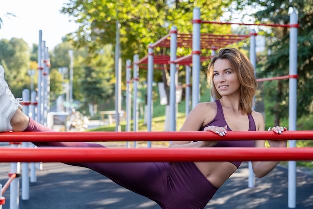 Atletisch meisje in fitnesskleding traint op straat en toont zich uitrekken terwijl ze bij de ongelijke tralies staat