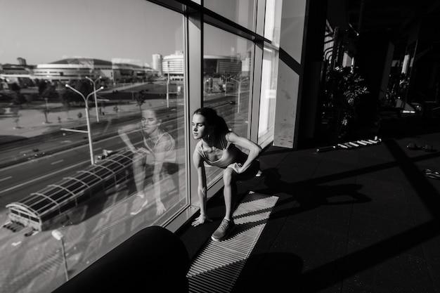 Atletisch meisje in sportkleding voert oefeningen met een halter, halters. fitness, training, gezonde levensstijl