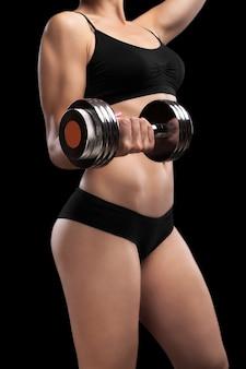 Atletisch meisje met dumbbells in de hand geïsoleerd op zwart.
