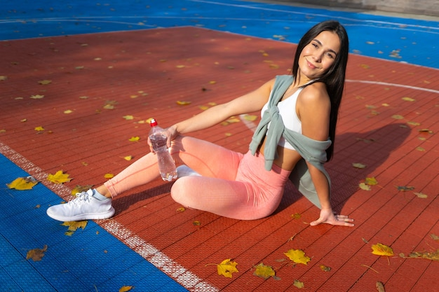 Atletisch meisje met een fles water in handen zit op een basketbalveld