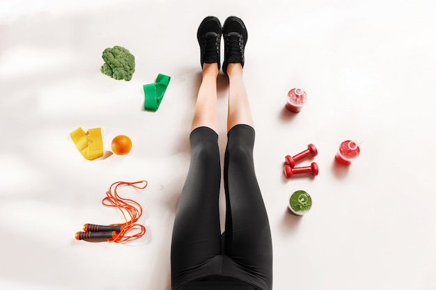 Atletisch meisje met gezond voedsel op de vloer