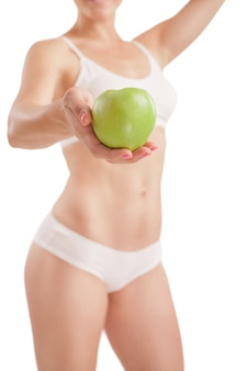 Atletisch meisje met groene appel in de hand.