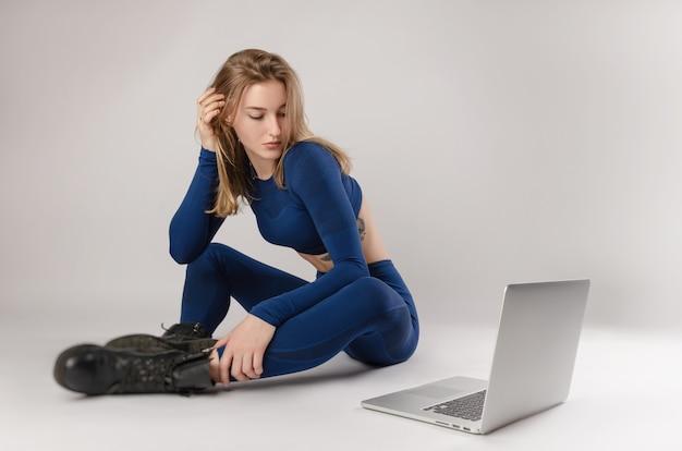 Atletisch meisje poseren in de studio die oefeningen online uitvoert op een laptop op een witte achtergrond