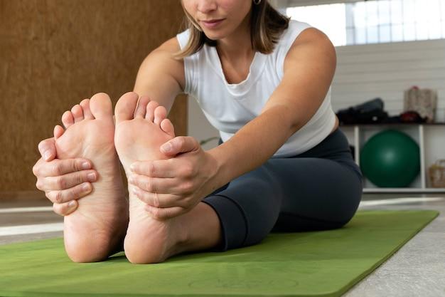 Atletisch mooi meisje doet yoga-oefeningen, zittende naar voren gevouwen pose (intense dorsal stretch), paschimottanasana, de wervelkolom, schouders, hamstrings strekken