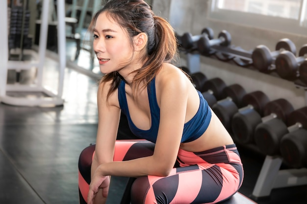 Atletisch mooie vrouw fit en gezond lachend in de sportschool na training.