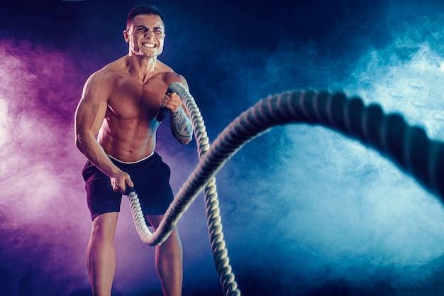 Atletisch ogende bodybulder traint met gevechtstouw op donker met rook. kracht en motivatie.