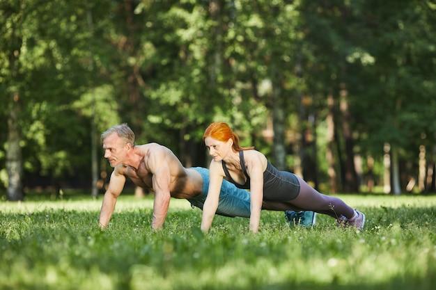 Atletisch ouder paar doet push-ups op gras tijdens het trainen samen in het park