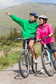 Atletisch paar op een fietsrit die verbindingsdraden met een kap met mens het richten dragen