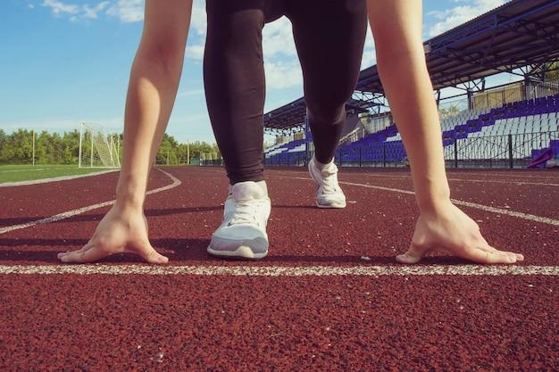 Atletisch tienermeisje in startpositie op het goede spoor. concept van vooruitgaan.