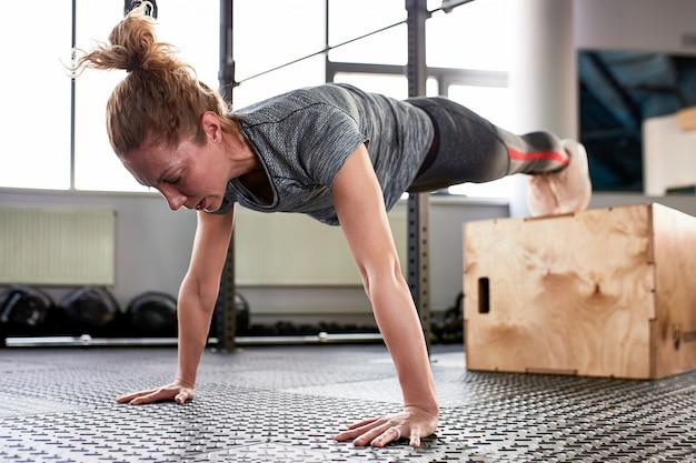Atletische aantrekkelijke vrouw uitgewrongen in de sportschool. trainingsconcept, sport, trainingsproces