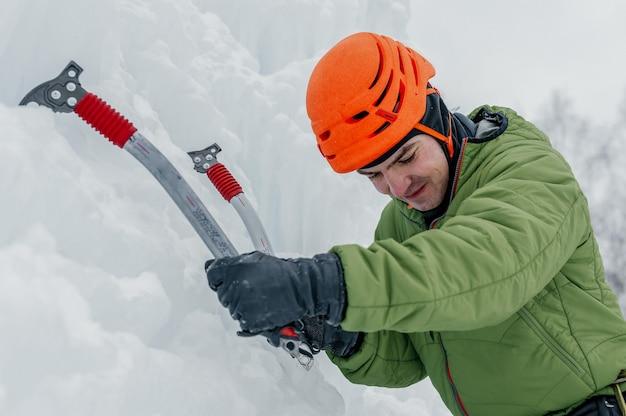Atletische alpinist man in oranje helm en ijs tools bijl klimmen een grote muur van ijs. buitensporten portret
