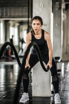 Atletische aziatische vrouw die met slagkabel uitoefenen bij gymnastiek