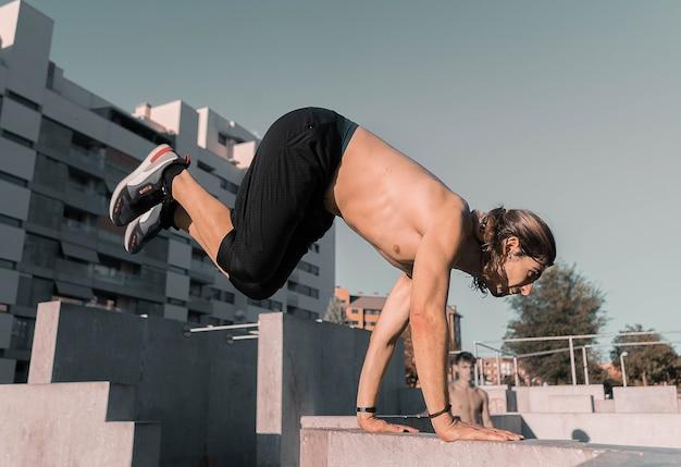Atletische blanke man doet parkour op gebouwen