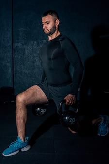 Atletische blanke man doet squats terwijl hij kettlebells opheft.