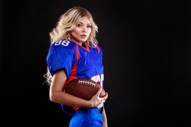 Atletische blonde die zich voordeed als amerikaans voetbal meisje op zwarte achtergrond. mooie jonge vrouw die de amerikaanse bal van de voetbal hoogste holding draagt. studiofoto van amerikaanse voetbalvrouw