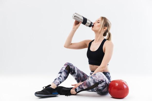 Atletische blonde vrouw 20s gekleed in sportkleding uit te werken en oefeningen te doen met fitness bal tijdens aerobics geïsoleerd over witte muur