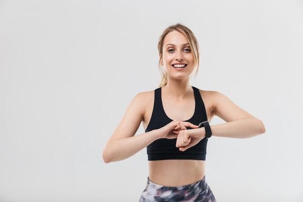 Atletische blonde vrouw gekleed in sportkleding trainen en kijken naar polshorloge tijdens fitness in sportschool geïsoleerd over witte muur