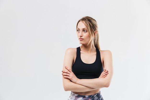 Atletische blonde vrouw gekleed in sportkleding uit te werken en oefeningen te doen tijdens fitness in sportschool geïsoleerd over witte muur