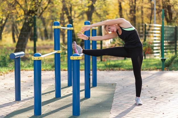 Atletische blondevrouw die uitrekkende oefeningen doen