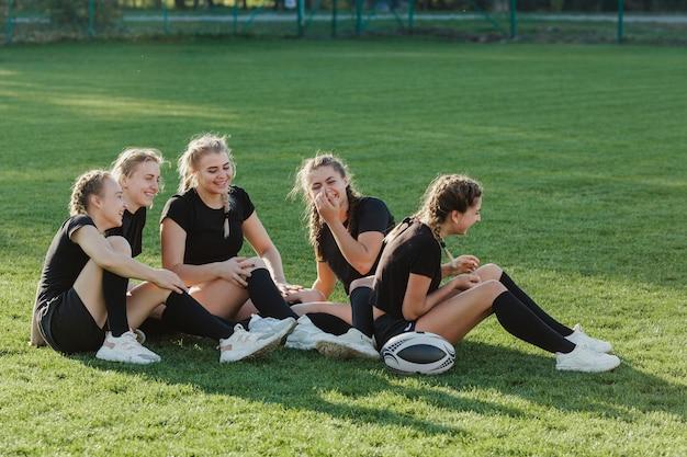 Atletische blondevrouwen die op gras zitten